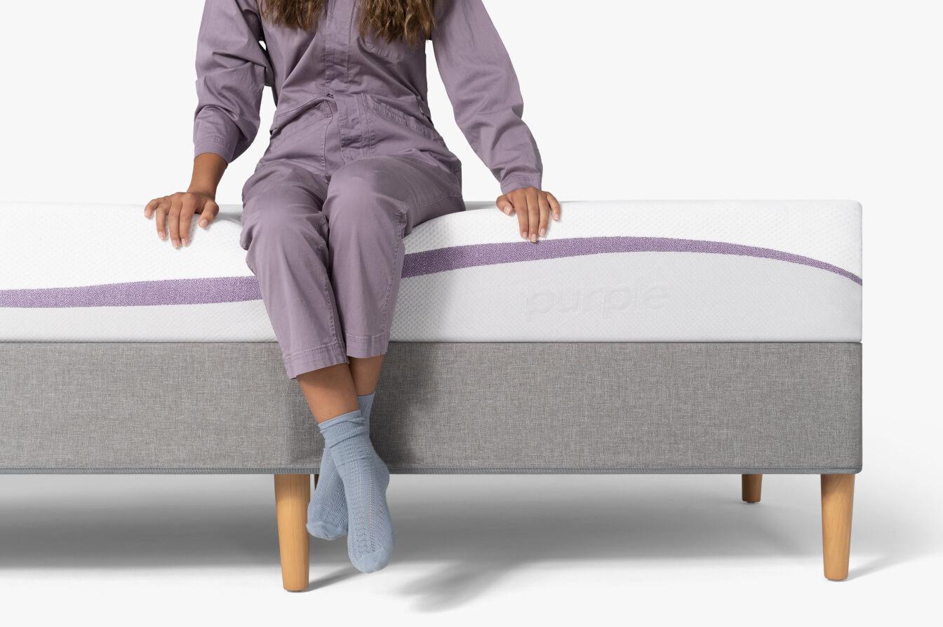 Teen Sitting On Purple Bed
